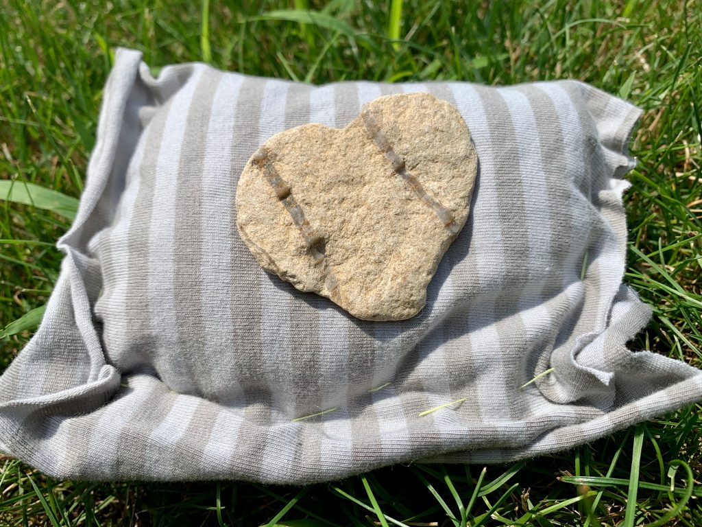 A tan rock with two parallel diagonal lines cutting through it is sitting on a handmade pillow of striped grey fabric. The pillow sits on the green grass in the sun.
